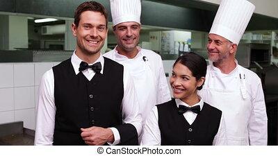 Happy restaurant staff smiling at c