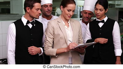 Happy restaurant staff with manager smiling at camera in a commercial kitchen
