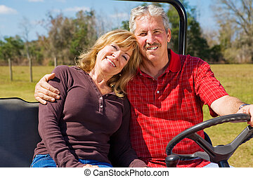 Happy Retired Couple - Good-looking retired couple riding...