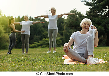 Happy retired woman beaming after exercising outdoors