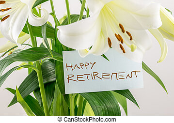 Happy Retirement gift of flowers with a handwritten note attached to a bouquet of pretty dainty white lilies with their green leaves, closeup view.