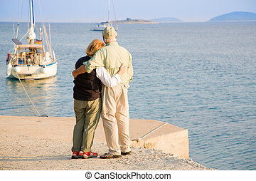 Happy retirement - Senior couple is watching sailboats off ...