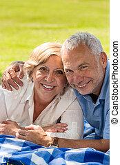 Happy retirement senior couple lying in grass