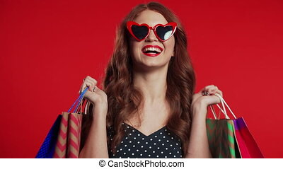 Happy retro styled young woman with red hair and paper bags after shopping isolated on studio background. Seasonal sale, purchases, spending money on gifts concept