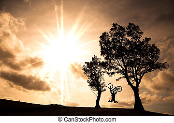 Happy rider holding bicycle and jumping on the hill