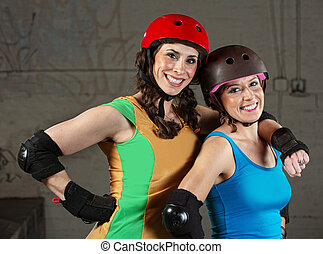 Pair of happy adult roller derby friends