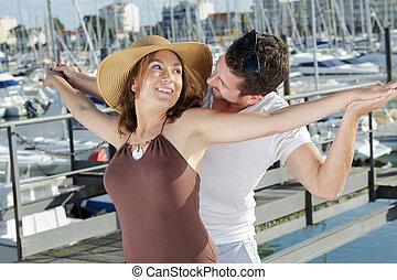 happy romantic attractive couple in love in a port
