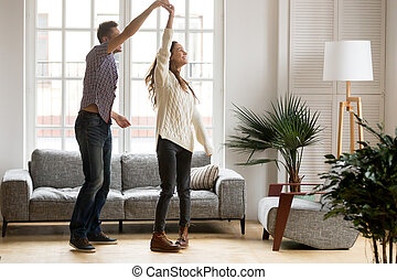 Happy romantic couple dancing in living room at home together