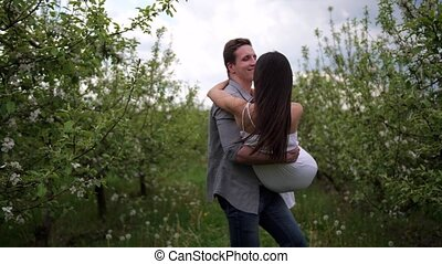 Happy romantic couple dating in blooming orchard
