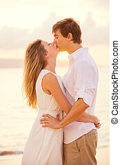 Happy romantic couple kissing on the beach at sunset, Man and woman in love