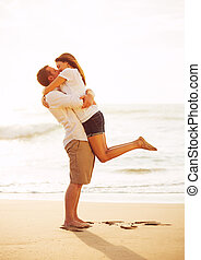 Romantic Couple Kissing on the Beach at Sunset