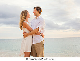Happy romantic couple on the beach at sunset embracing each other. Man and woman in love watching the sun set into ocean