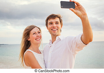 Happy romantic couple on the beach taking photo of themselves with smart phone at sunset, Man and woman in love