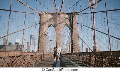 Happy romantic couple run forward along Brooklyn Bridge in New York City, hold hands on a beautiful sunny summer day.
