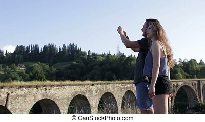 Happy romantic couple tourists in front of old bridge make photo