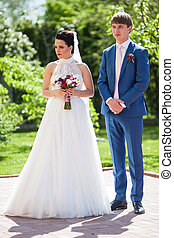 Happy, romantic newlywed couple posing in sunny park
