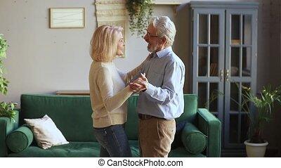 Happy romantic old senior couple dancing waltz in living room