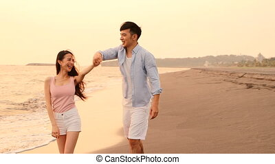 Happy Romantic young Couple dancing on the beach at sunset