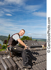 Happy roofer working on a roof tile