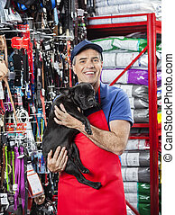 Happy Salesman Carrying French Bulldog In Pet Store