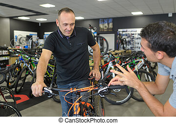 happy salesman giving bicycle to customer at bicycle stores