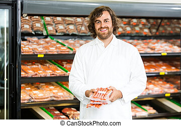 Happy Salesman Holding Meat Packages At Counter - Portrait...