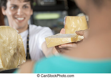 Happy Salesman Selling Cheese To Female Customer