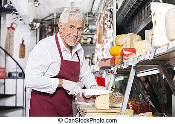 Happy Salesman Slicing Cheese In Shop