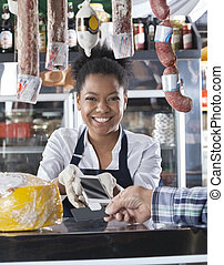 Happy Saleswoman Accepting Credit Card Payment From Customer