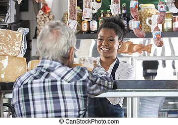 Happy Saleswoman Selling Cheese To Male Customer