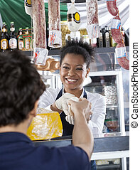 Happy Saleswoman Selling Cheese To Customer At Shop - Happy...