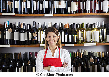 Happy Saleswoman Standing Against Shelves In Wine Shop