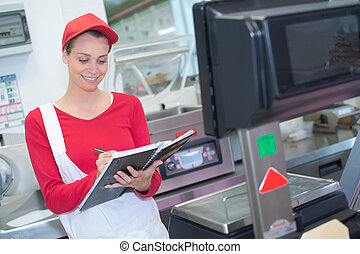 happy saleswoman weighing meat at the supermarket