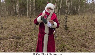 Happy Santa Claus with gifts dancing in woods