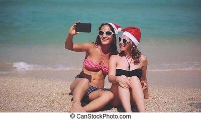 Happy santa girls wearing santa hat on a sunny beach taking a selfie with smartphone having fun. Christmas modern technology concept. 1920x1080