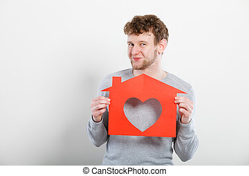 Happy satisfied man with heart house.