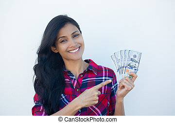 Closeup portrait, excited successful young business woman in plaid shirt holding money dollar bills in hand isolated white wall background. Positive emotion facial expression feeling. Financial reward