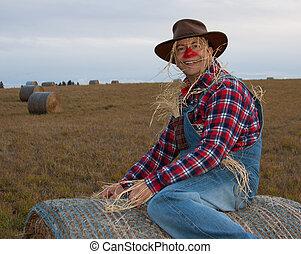 Happy scarecrow sitting on haybale.