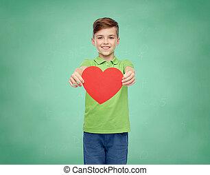happy school boy holding red heart shape