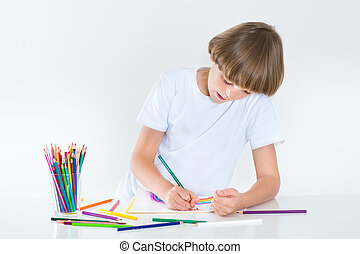 Happy school boy paiting at a white desk
