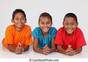 Happy school friends lying on floor - Group of three happy...