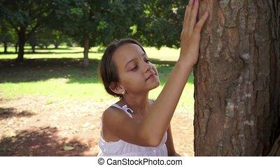 Happy school girl hugging tree