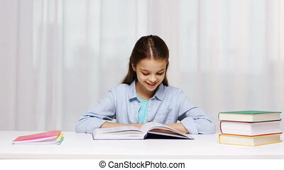 happy school girl reading book or textbook at home