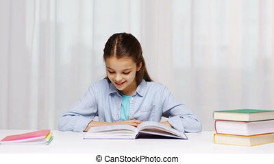 happy school girl reading book or textbook at home -...