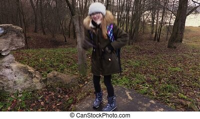 Happy school girl with backpack dancing in the park