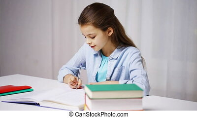 happy school girl with books and notepad at home -...