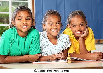 Happy school girls reading a book