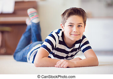 Happy schoolboy 9 years old  lying on floor at home