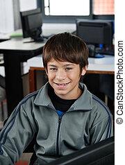 Happy Schoolboy Sitting In Computer Class