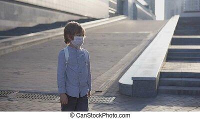 Happy schoolboys in medical mask meet in school yard and ...